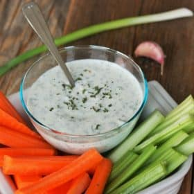 homemade ranch dressing in a bowl with veggies on a wooden board