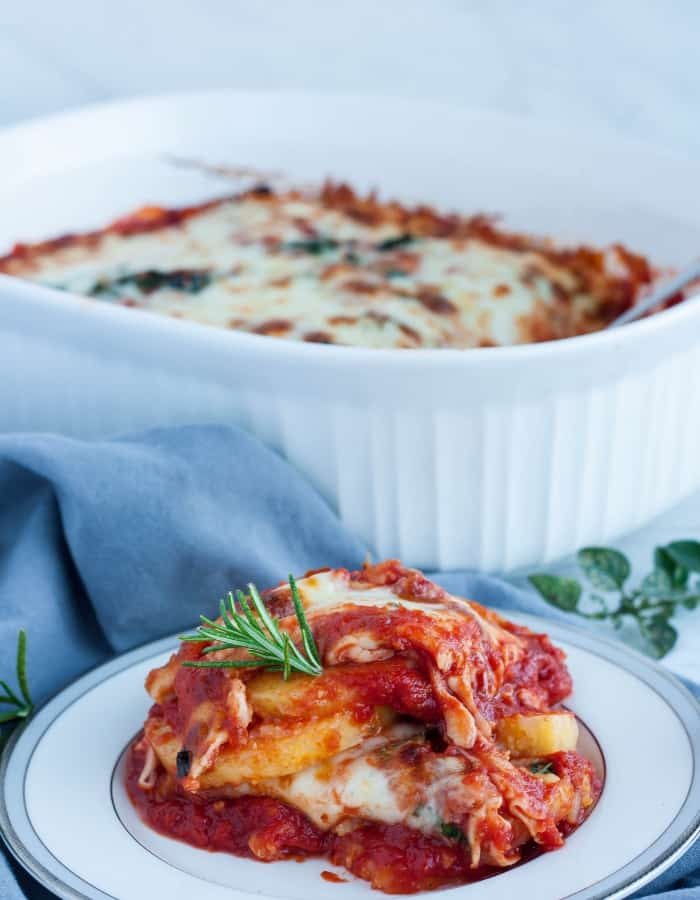 a plate and dish of gluten-free lasagna with herbs