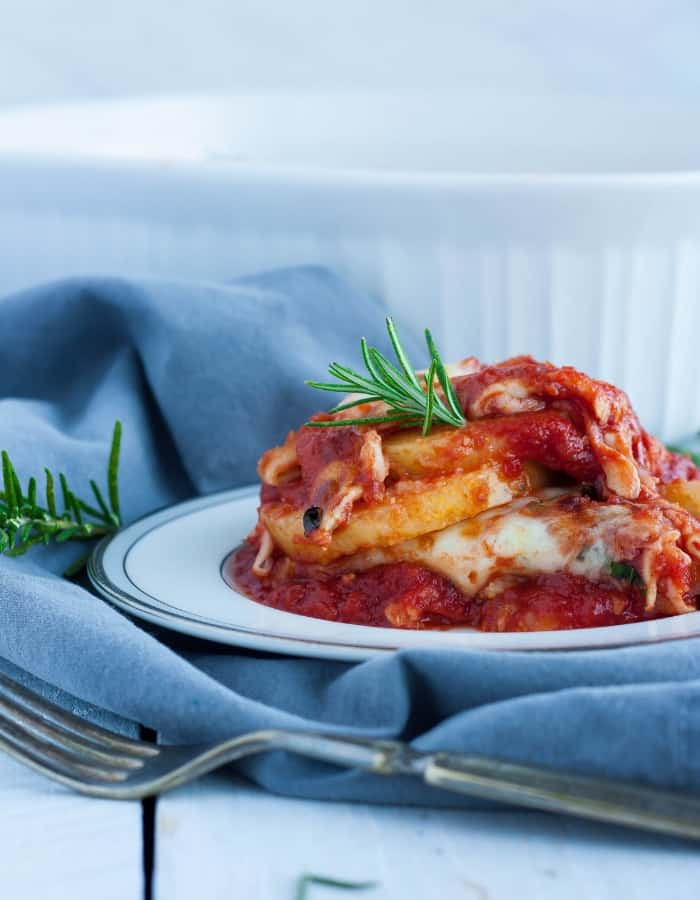 a plate of gluten free lasagna on a grey cloth