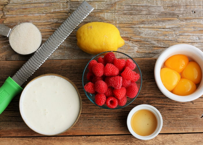 Cream, sugar, lemon, raspberries, and egg yolks on a wooden board