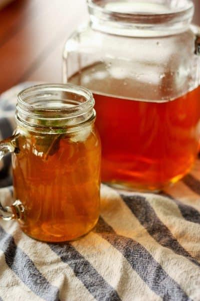 Healthy Sweet Tea in a mason jar mug with a half-full pitcher behind it
