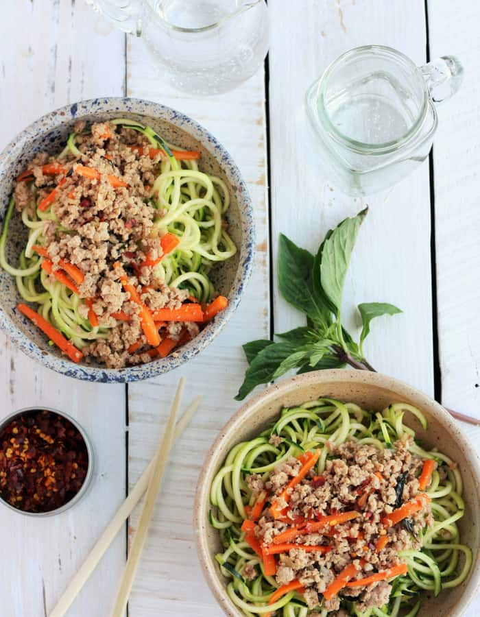 Two bowls of Basil Thai Chicken with zoodles, basil, glasses, and chopsticks on a white board