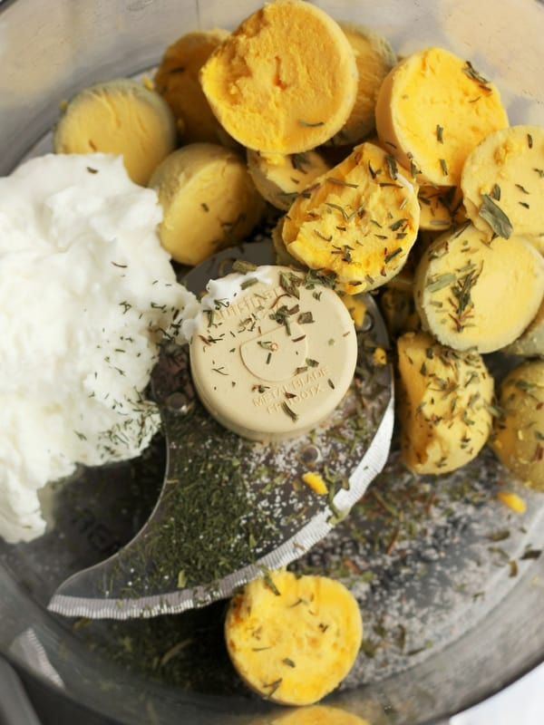 egg yolks, greek yogurt, and herbs in a food processor
