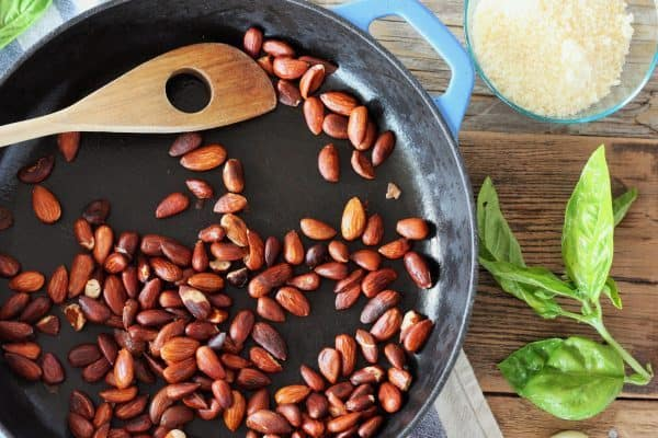 toasted almonds in a blue cast iron skillet with parmesan and fresh basil on a wooden backdrop