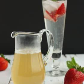 A small glass pitcher of honey simple syrup in front of a glass with strawberries, mint, and sparkling water