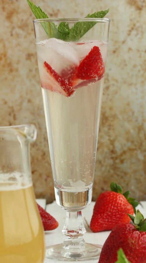 A glass of sparkling water with strawberries and mint