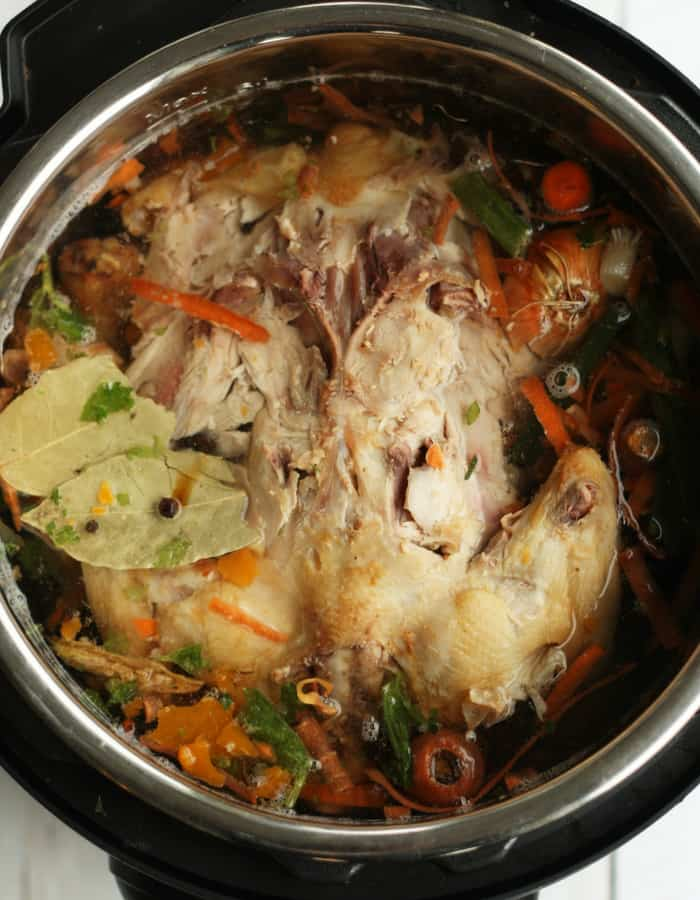 a whole chicken in an Instant Pot filled with water and vegetables