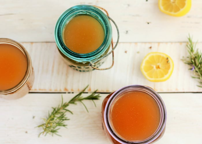 Three different jars of chicken stock on a white board with rosemary and lemons