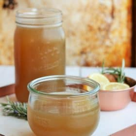 homemade chicken stock in jars on a white tray with rosemary and lemon