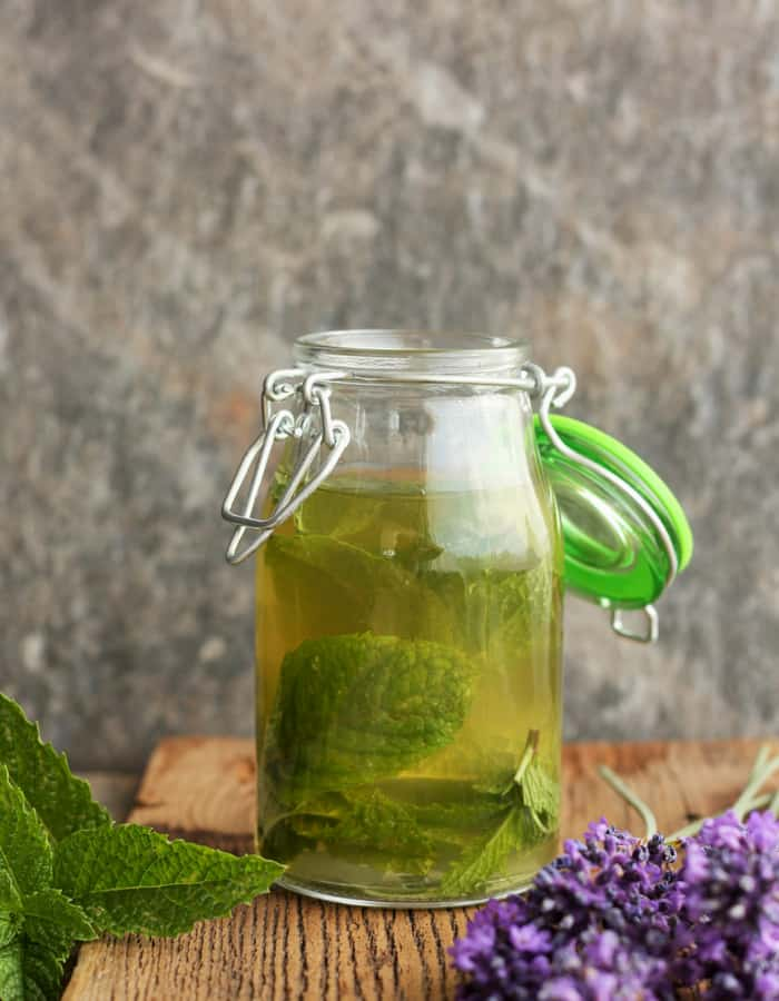 A bottle of homemade peppermint extract with mint and lavender on a wooden board