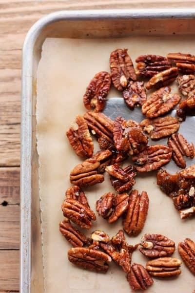 candied pecans on a parchment-lined baking pan