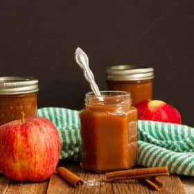 jars of slow cooker apple butter with apples and cinnamon sticks