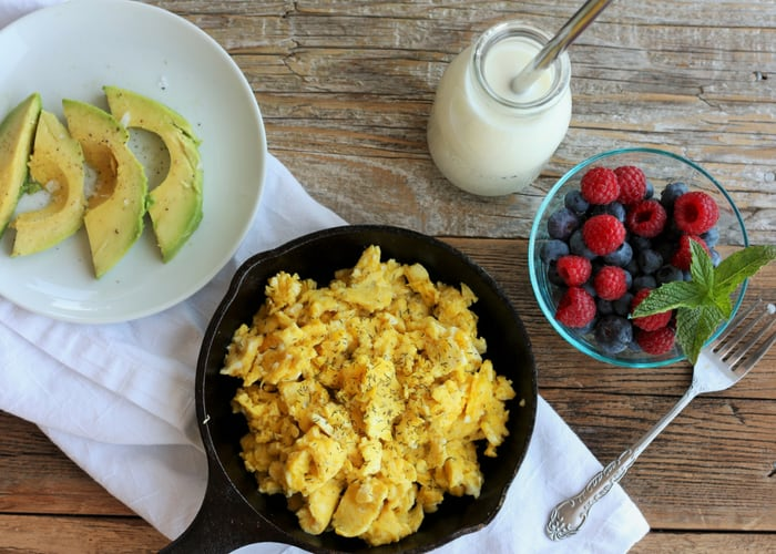 scrambled eggs in a cast iron skillet with berries, milk, and avocado