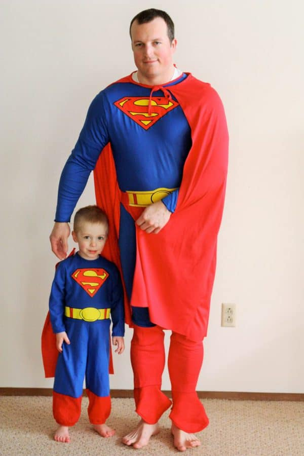 a father and son in superman costumes