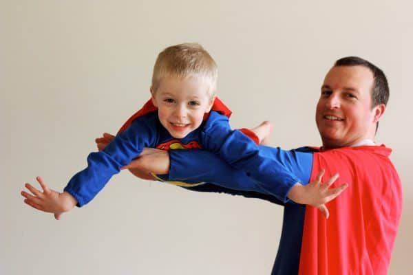 a father in a superman costume holding a child in a superman costume