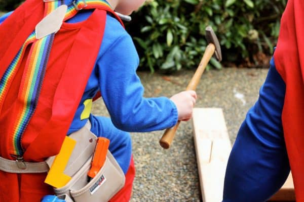 a child nailing a hammer to build a raspberry support