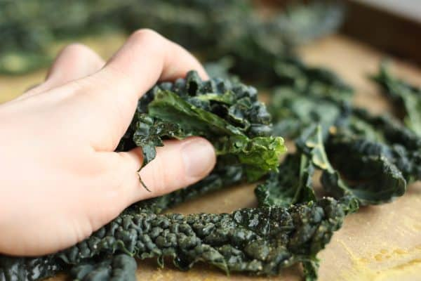 a hand massaging kale