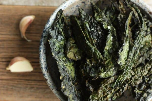 kale chips in a bowl with garlic on a wooden board