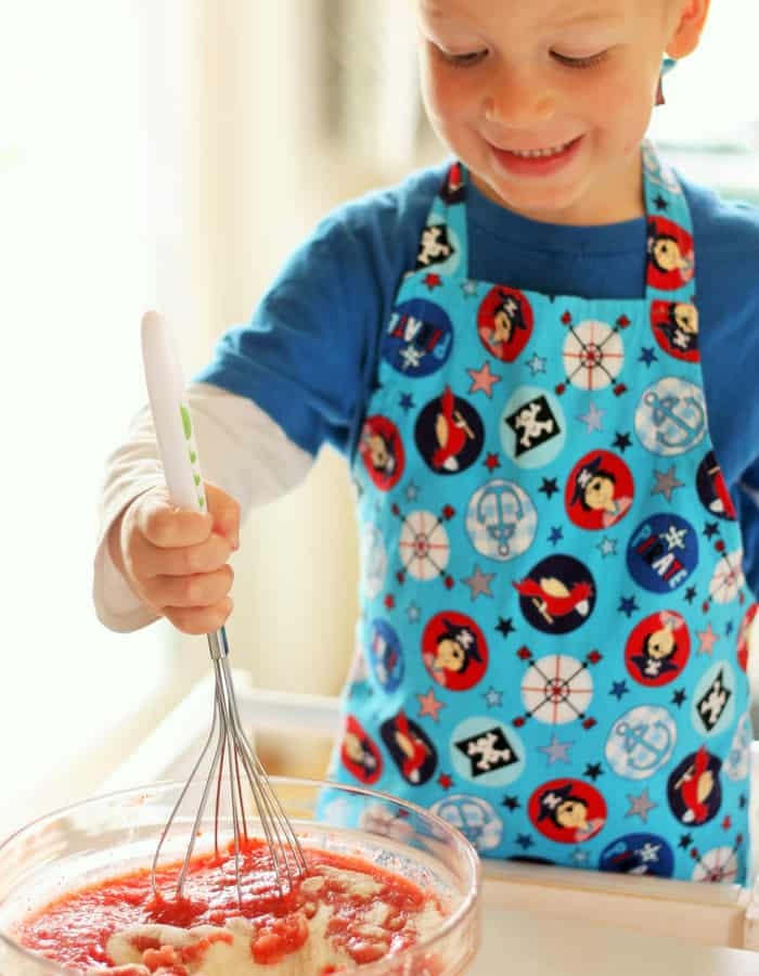 a little boy in an apron making strawberry freezer jam