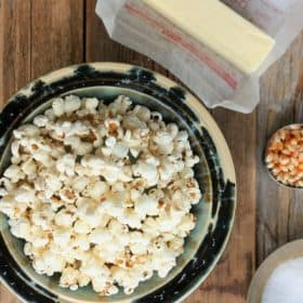 a bowl of stove top popcorn, butter, and salt