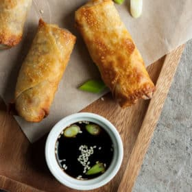 Three air fryer egg rolls on a wooden tray with a dish of soy sauce
