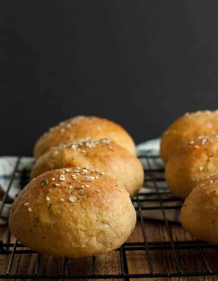 whole wheat hamburger buns on a baking rack against a black background