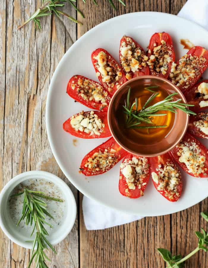 feta stuffed grilled tomatoes on a plate with olive oil and herbs