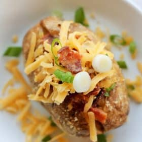 baked potato on a dish with lots of toppings