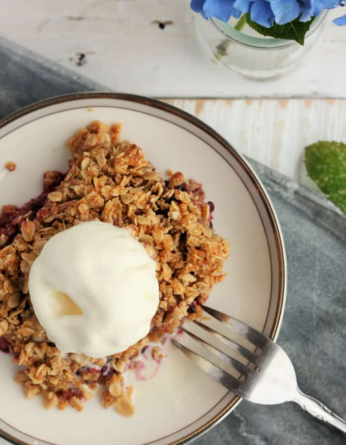 blackberry crisp with ice cream on a plate with a fork