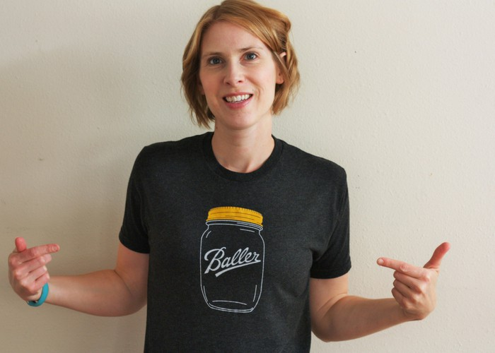 A woman wearing a shirt that says baller in a canning jar