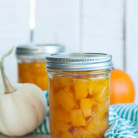 Jars of canned pumpkin with two mini pumpkins and a green striped cloth