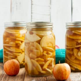 three jars from canning apple pie filling on a wooden board