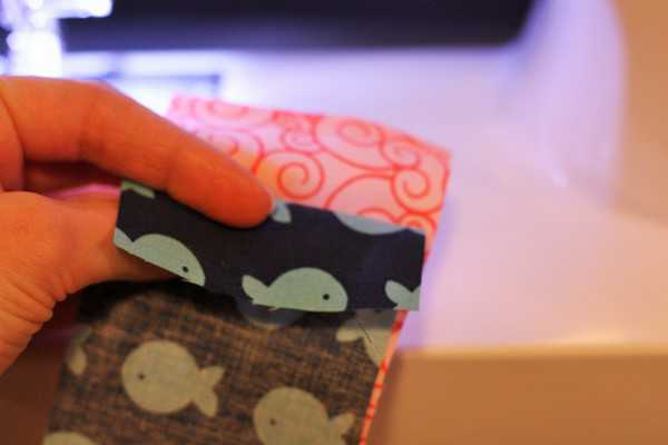 a hand holding two pieces of fabric while making beginner quilts