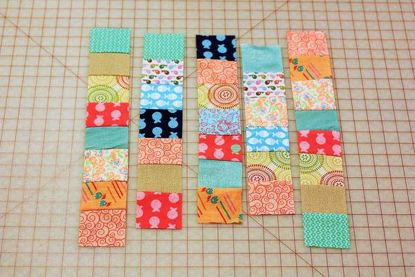 individual strips of fabric laid out on a cutting mat for beginner quilts