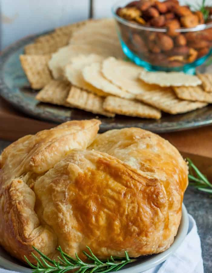 a close up photo of baked brie in puff pastry with roasted garlic and crackers