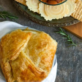 baked brie in puff pastry with a plate of crackers and rosemary