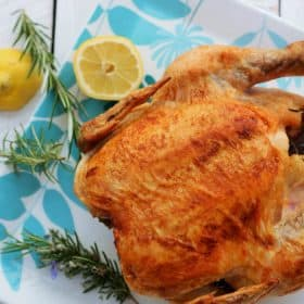 Roasted chicken on a platter with lemons and fresh rosemary