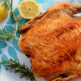 Roasted chicken on a white platter with rosemary and fresh lemons