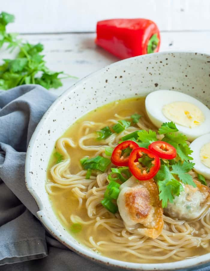 a large ramen noodle bowl with peppers and hard boiled eggs