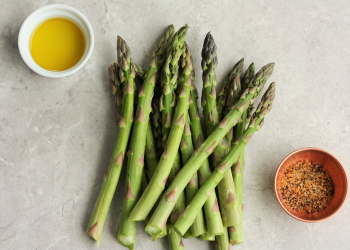 grey tray with fresh asparagus, a bowl of olive oil, and a bowl of seasoning