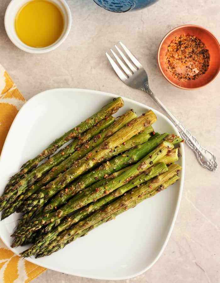 A plate of roasted asparagus on a tray with a fork and seasoning