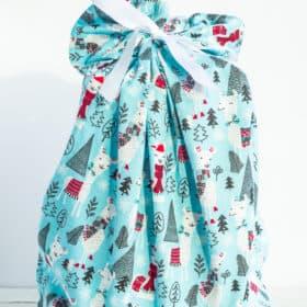 a blue fabric gift bag with holiday llamas