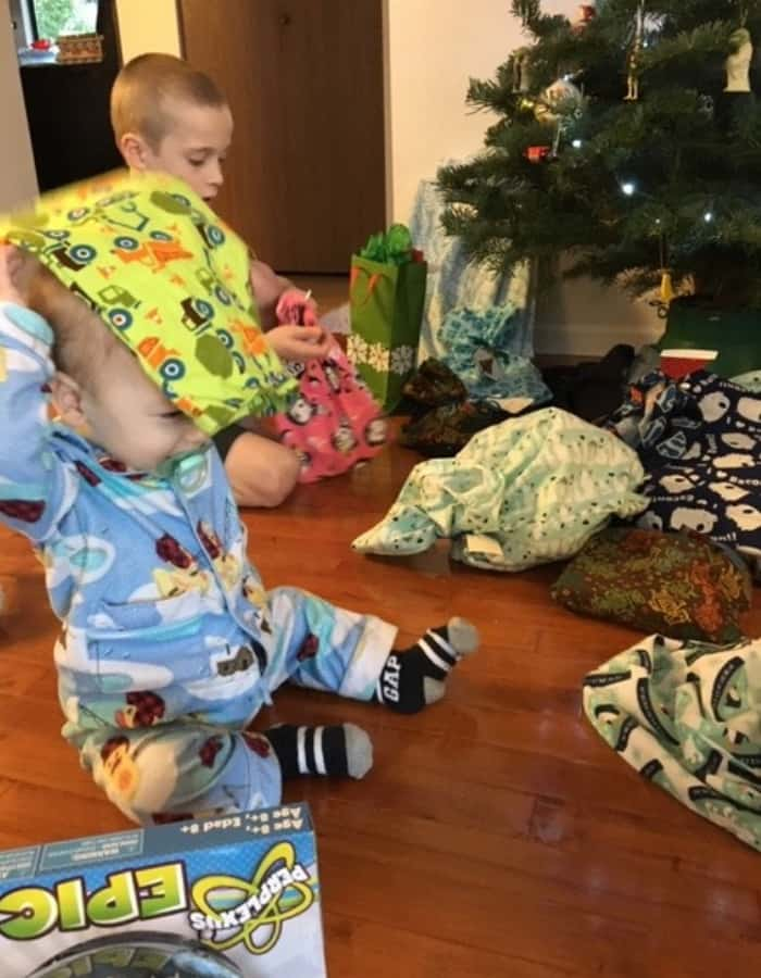 Two kids opening Christmas presents wrapped in reusable gift bags