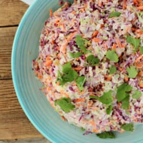 A bowl of spicy easy coleslaw in a blue bowl on a wooden board
