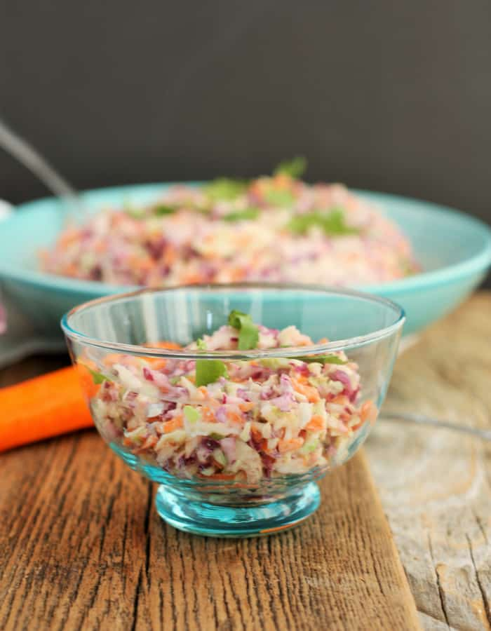 two bowls of easy coleslaw on a wooden board