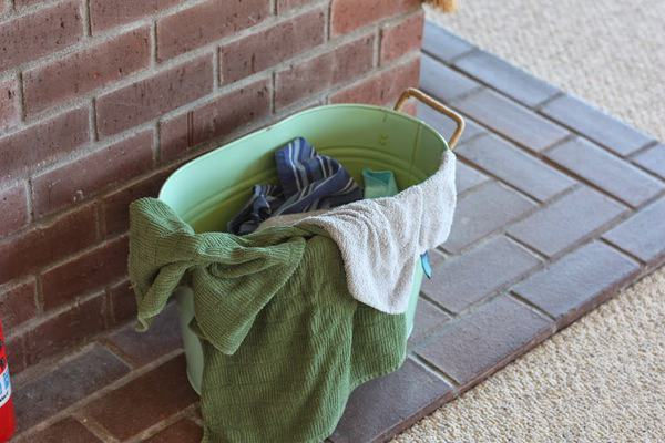 a green metal bin with dirty rags it in sitting on bricks