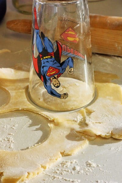a Superman drinking glass making circles in pie crust