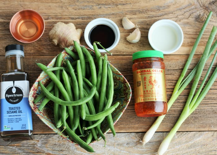 A wooden board with green beans, sesame oil, garlic, green onion, and ginger