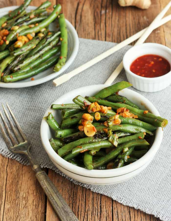 Two bowls of green bean stir fry with spicy chili paste and a fork on a wooden board
