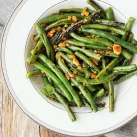 a round white plate full of green bean stir fry